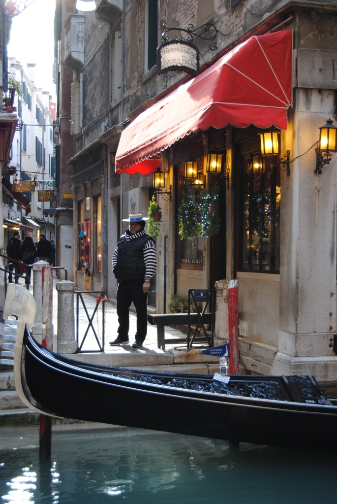 A gondolier taking a break, while watching his gondola.