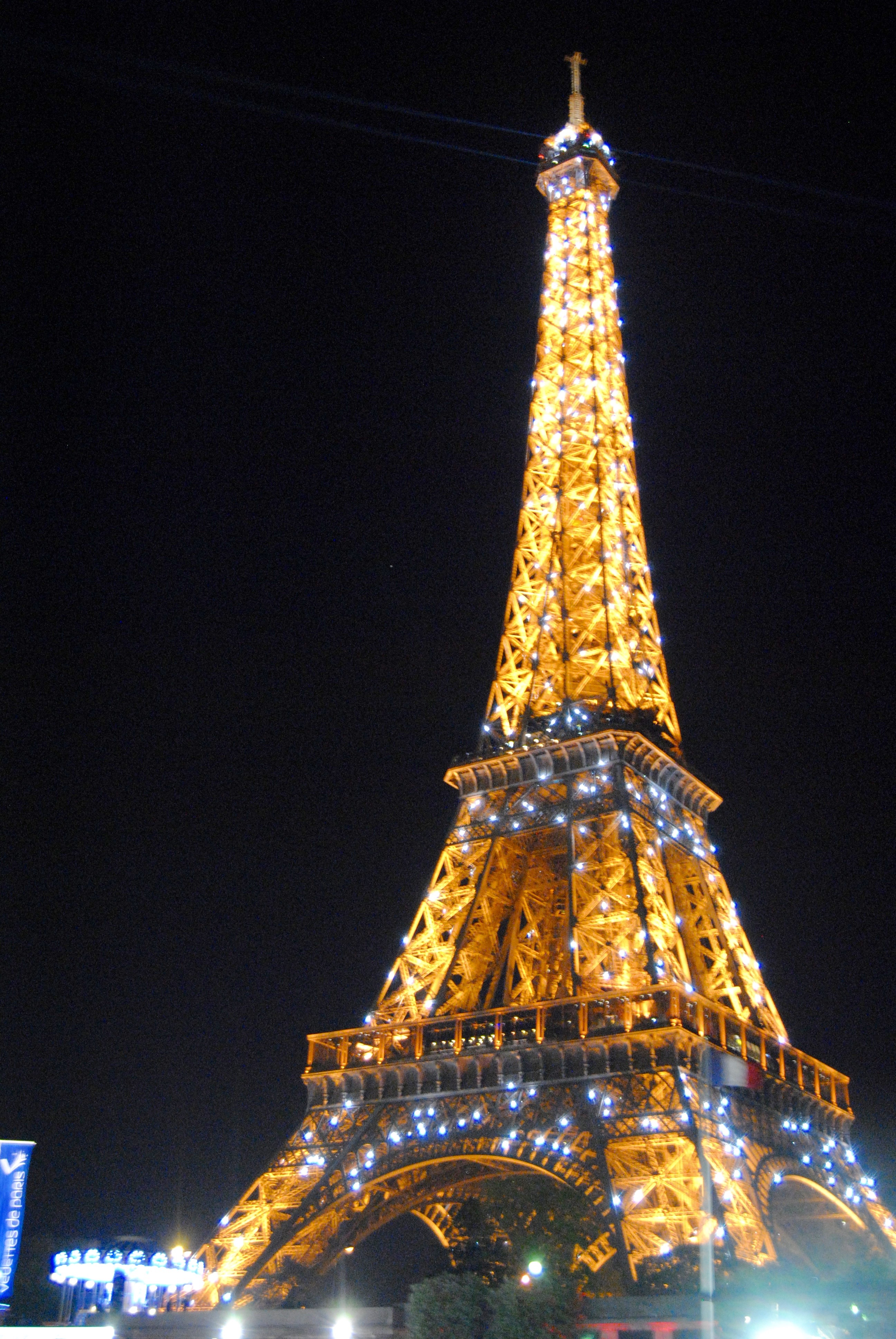 The Eiffel Tower sparkling at night.