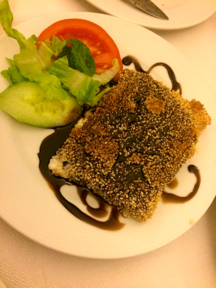 The feta cheese covered in sesame and drizzled with balsamic vinaigrette.