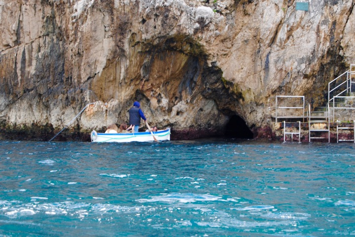 The small hole to the right of the row boat is the entrance to the Blue Grotto.